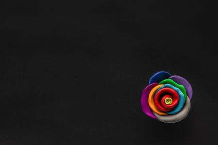 A flower made from multicolored plasticine on black background , shot from above, aligned at the bottom right. Stock Photo