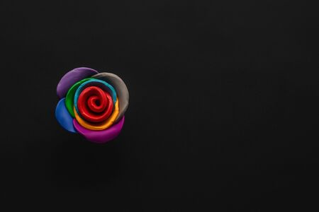 A flower made from multicolored plasticine on black background , shot from above, aligned to the left. Stock Photo