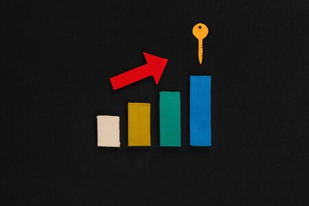 A graph made from a red arrow on top of colored columns pointing towards a key on black background, shot from above.