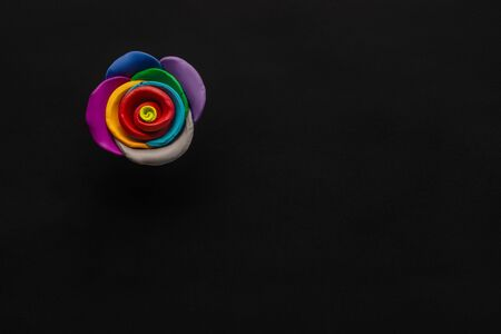 A flower made from multicolored plasticine on black background , shot from above, aligned at the top left.