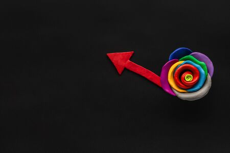 A flower made from multicolored plasticine with an arrow pointing up from it on black background, shot from above.