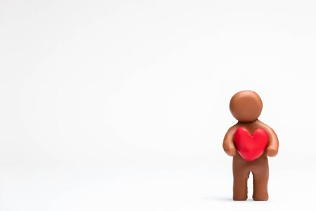 A man made from plasticine holding a heart on white background, aligned to the right.