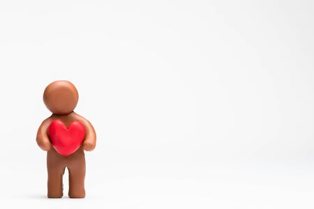 A man made from plasticine holding a heart on white background, aligned to the left.