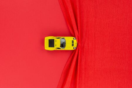 A yellow car figurine on a red wrinkled background, shot from above. 免版税图像
