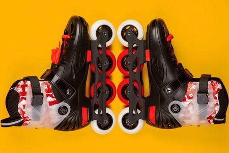 A pair of red roller skates on yellow background , shot from above. 免版税图像