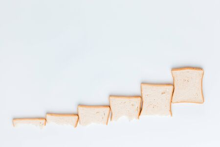 A line of slices of bread which are getting bigger and bigger, on a white background, shot from above. Imagens