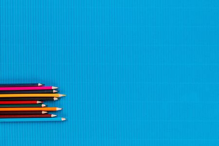 A bunch of colorful crayons of different sizes arranged randomly on an ocean blue background, shot from above, aligned at the bottom left. Banque d'images
