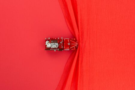 A red car figurine on a red wrinkled background, shot from above.