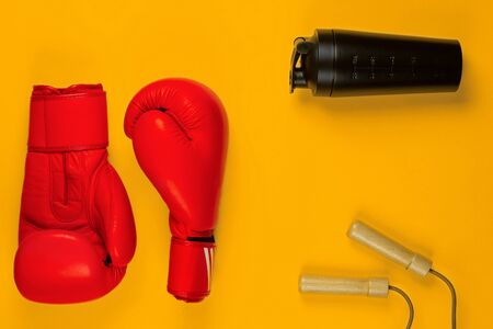 A pair of red boxing gloves next to a black water bottle and a jump rope, on yellow background, shot from above.