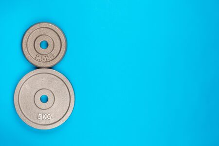 A pair of weights on blue background, shot from above.