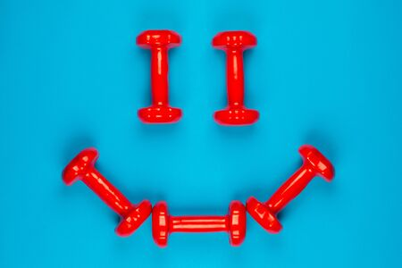 A smiley face made from red dumbbells on blue background, shot from above.