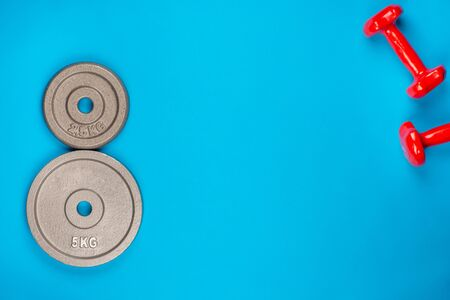 A pair of weights and a pair of dumbbells on blue background, shot from above. 版權商用圖片