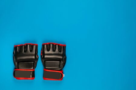 A pair of black fighting gloves on blue background, shot from above.
