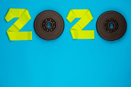 The year 2020 written with weights and stripes, on blue background, shot from above.
