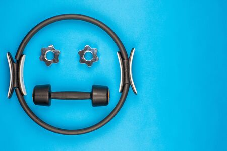 A smiley face made from gym equipment, on blue background, shot from above. 版權商用圖片