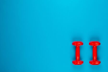 Two red dumbbells on blue background, shot from above, aligned at the bottom right. 版權商用圖片