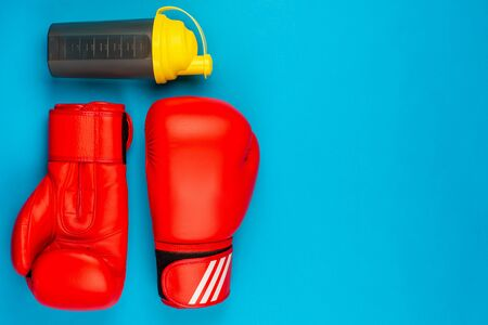 A pair of red boxing gloves next to a water bottle , on blue background , shot from above. 版權商用圖片
