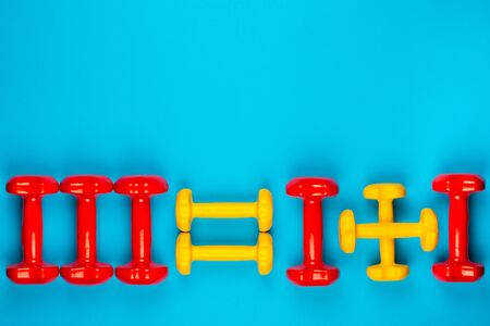 Three red dumbbells equaling one dumbbell plus another one, on blue background, shot from above. 版權商用圖片