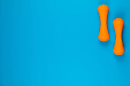 Two orange dumbbells on blue background, shot from above, aligned at the top right.