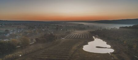 A beautiful shot of a lake near surrounded by fields and trees in the evening, aerial view.