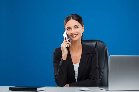 Beautiful and young businesswoman sitting at her desk listening carefully to her phone, isolated on blue background. Banco de Imagens