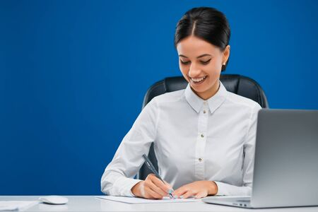 Beautiful, young businesswoman sitting at her desk before a laptop writing with enthusiasm her ideas on a sheet of paper, isolated on blue background.