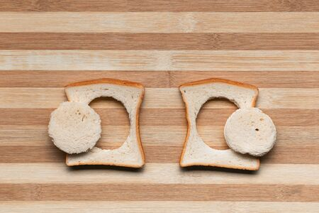 Two slices of bread with their centers cut on a brown table, shot from above. Reklamní fotografie