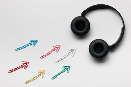 Many small colorful arrows pointing towards a set of headphones on white background, shot from above.