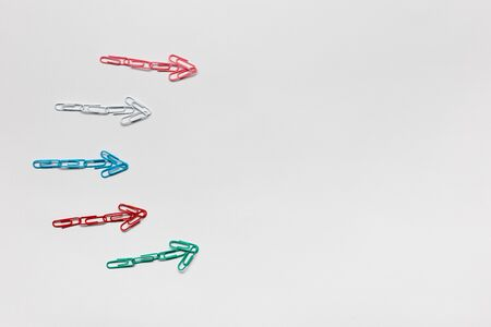 Many small colorful arrows pointing towards the right on white background, shot from above. Stockfoto