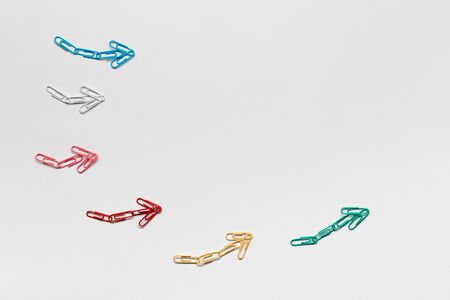 Many small colorful arrows pointing upwards on white background, shot from above.