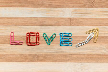 The word love next to an arrow pointing upwards all made from colorful paperclips on a table, shot from above, aligned in the center closeup..
