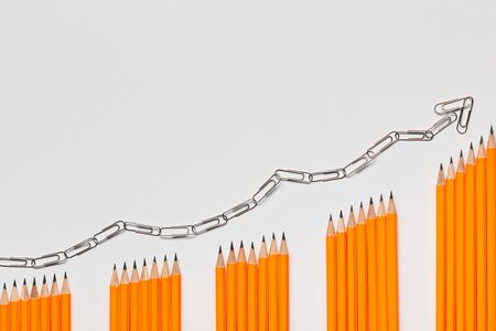 A bunch of pencils arranged in columns in an ascending order on white background, shot from above. closeup.