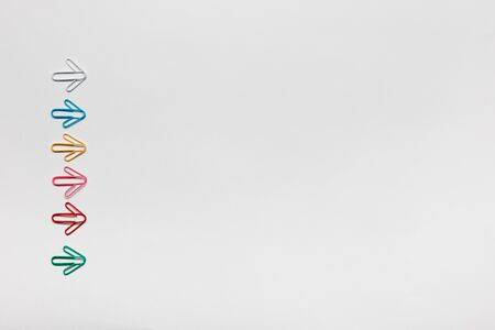 Many small colorful arrows on white background, shot from above, aligned to the left. Stockfoto
