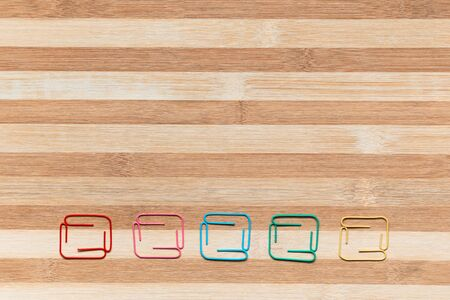 Many small colorful squares on a table, shot from above, aligned at the bottom.