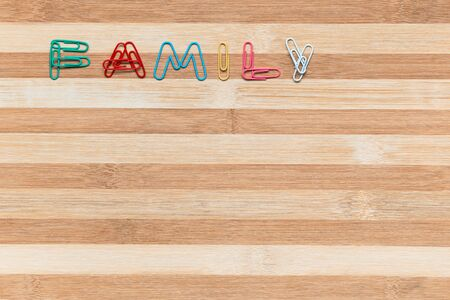 The word family made from colorful paperclips on a table, shot from above, aligned at the top left.