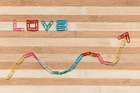The word love next to an arrow pointing upwards all made from colorful paperclips on a table, shot from above.