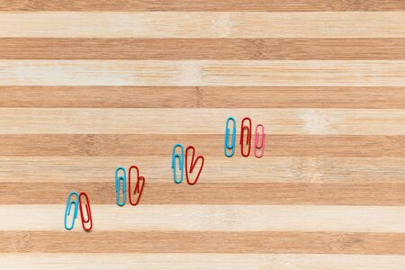 Colorful paperclips on a table, shot from above, arranged diagonally from bottom left towards the top right.