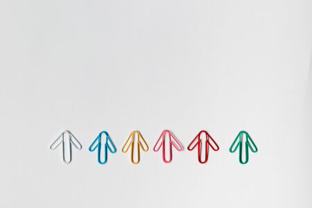 Many small colorful arrows on white background, shot from above, aligned at the bottom.