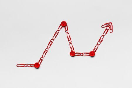 A graph moving upwards made from red paperclips on white background, shot from above,closeup.