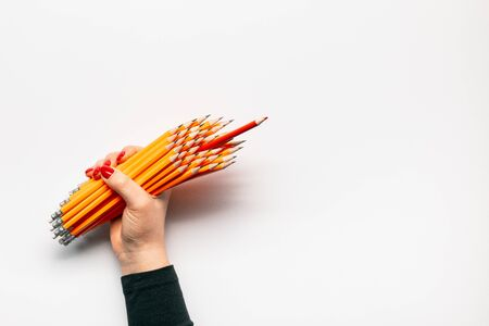 A hand holding a bunch of pencils on white background , shot from above.