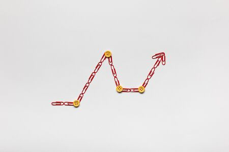 A graph moving upwards made from red paperclips on white background, shot from above.