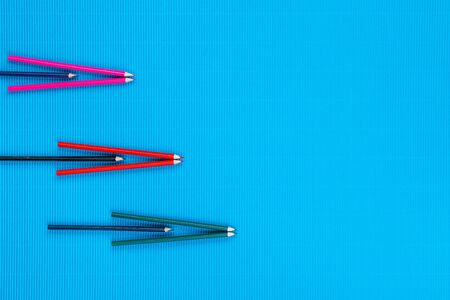 A bunch of colorful crayons forming arrows on an ocean blue background, shot from above , arranged to the left. Фото со стока