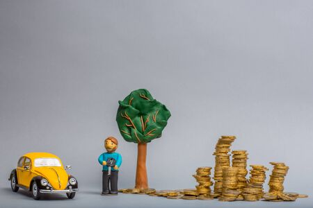 Plasticine man holding a key under a plasticine man in between a yellow car figurine and a big pile of golden coins, on gray background.