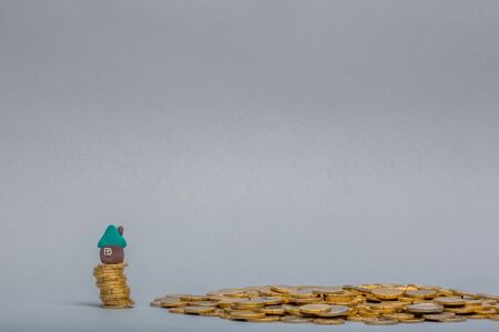 Small plasticine house model placed on a column made from golden coins next to a pile of coins, on gray background.