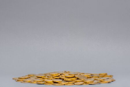 Big pile of golden coins isolated on gray background. Banco de Imagens