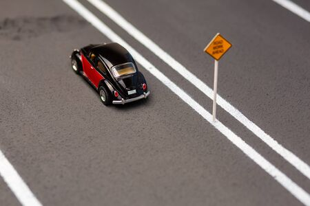 Crimson car figurine on the highway model in front of a big hole, shot from above. 版權商用圖片