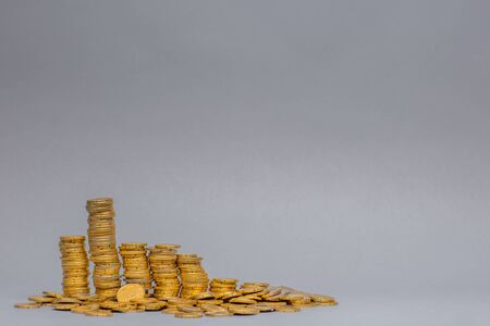 Stack of golden coins, on gray background.