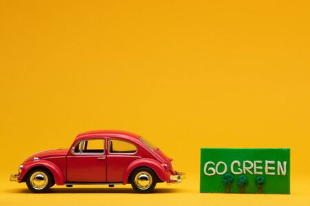 Cool red car figurine aligned to the left next to a green sign with the words go green on it, on orange background. Stock Photo