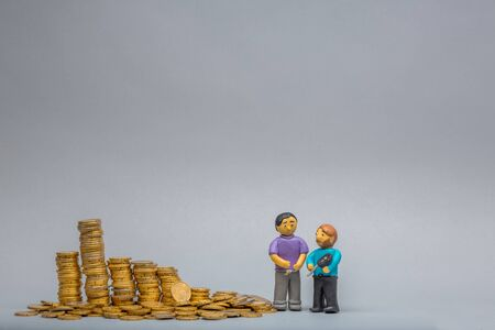 Two tiny men made from plasticine standing next to a big heap of golden coins, on gray background.