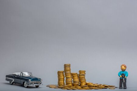 Big pile of golden coins in between a retro, blue car figurine and a plasticine man holding key, on gray background.